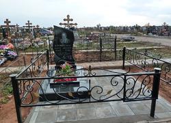Гранитный памятник с металлической оградкой